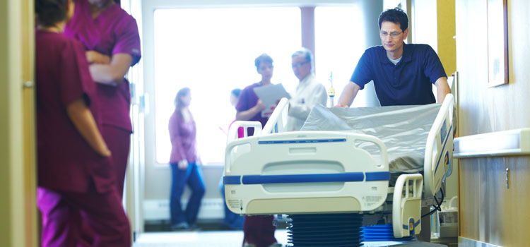 An Agiliti team member pushes a specialty bed down a busy hospital hallway